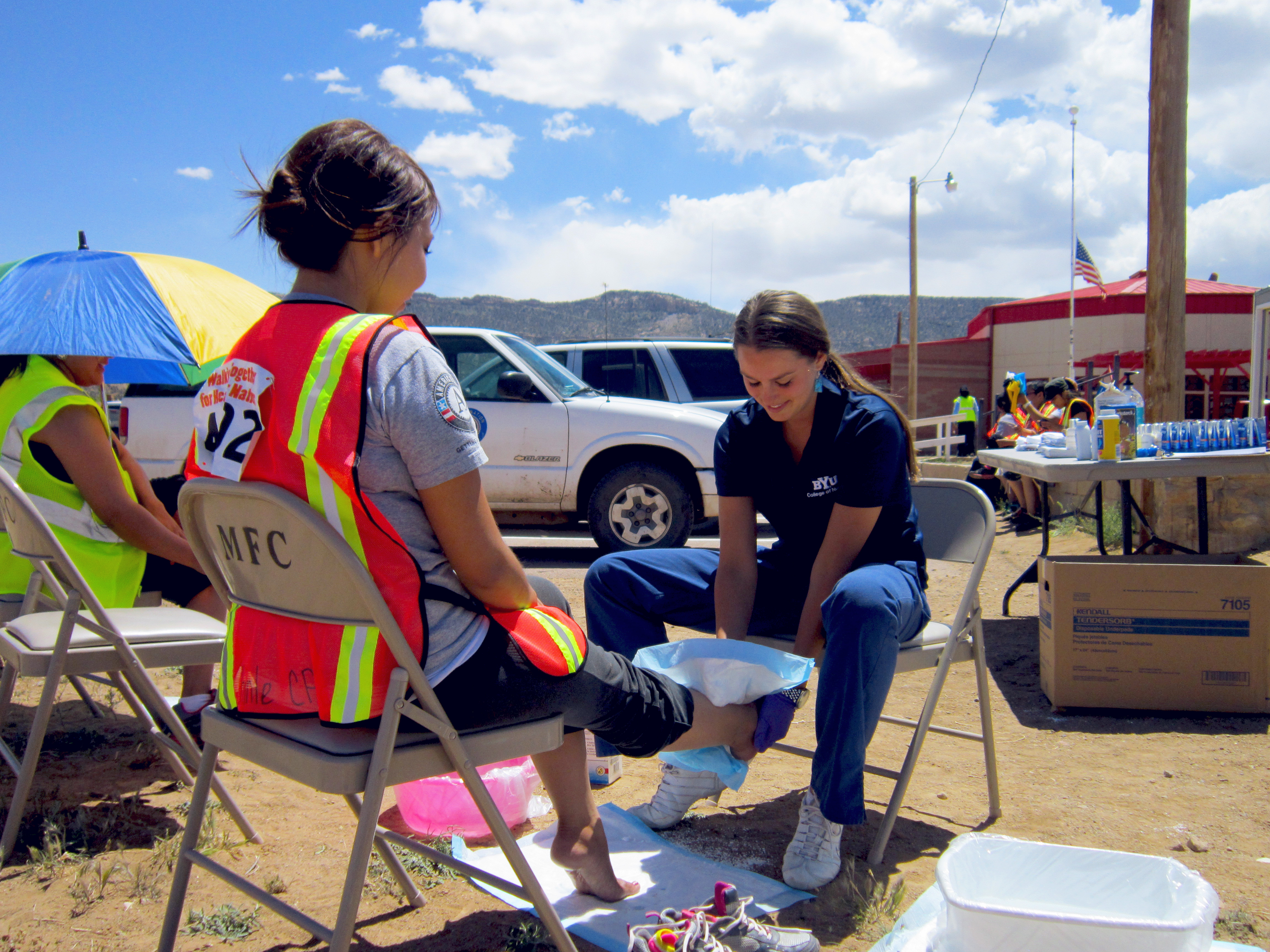 Student nurse providing foot care for a Navajo woman participating in Diabetes Awareness Walk